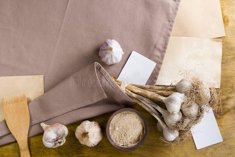 Heads of garlic and garlic powder. On a linen napkin stock photography