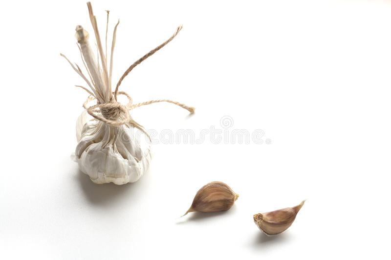 Heads of young and mature garlic, and raw cloves of garlic isolated on a white background. stock photo