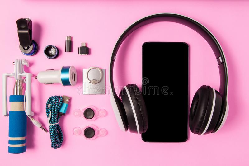 The Headset listen music with mobile phone and Accessory set technology Blank space on bright pink background. Headset listen music with mobile phone and stock images