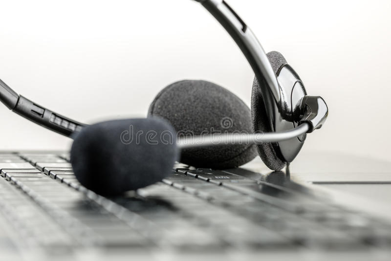 Headset lying on a laptop computer stock photo