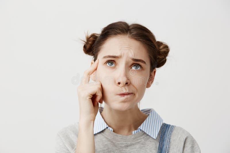 Headshot ενήλικο να ανατρέξει κοριτσιών με το συνοφρύωμα που εκφράζει την παρανόηση Χαριτωμένη γυναίκα σπουδαστής που στρίβει το  στοκ φωτογραφία