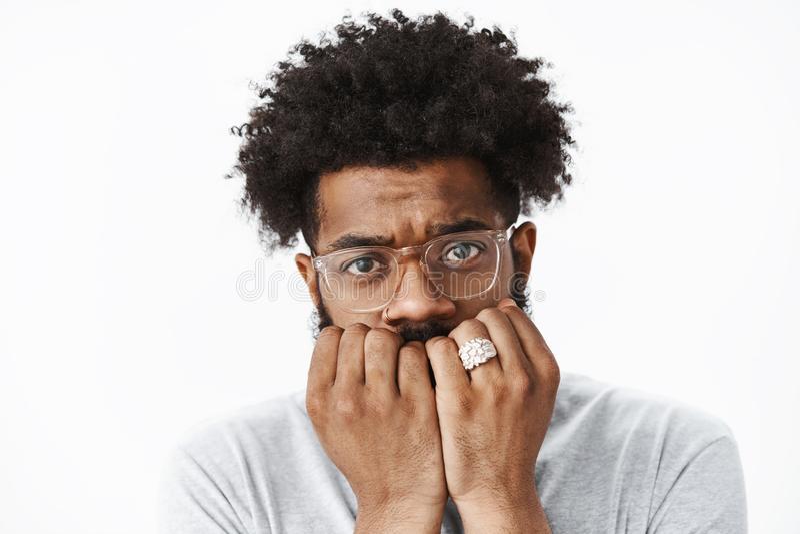 Headshot του ανήσυχου και φοβησμένου αρσενικού συνεσταλμένου τύπου με το afro hairstyle στα γυαλιά που δαγκώνουν τα νύχια και που στοκ φωτογραφία με δικαίωμα ελεύθερης χρήσης