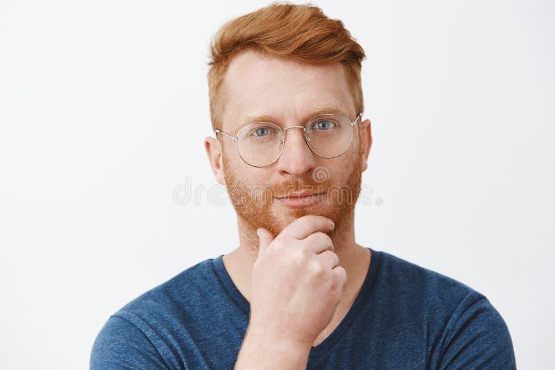 Headshot του δημιουργικού και έξυπνου όμορφου redhead τύπου με τη σκληρή τρίχα στα γυαλιά και την μπλε μπλούζα, που τρίβει τη γεν στοκ εικόνες