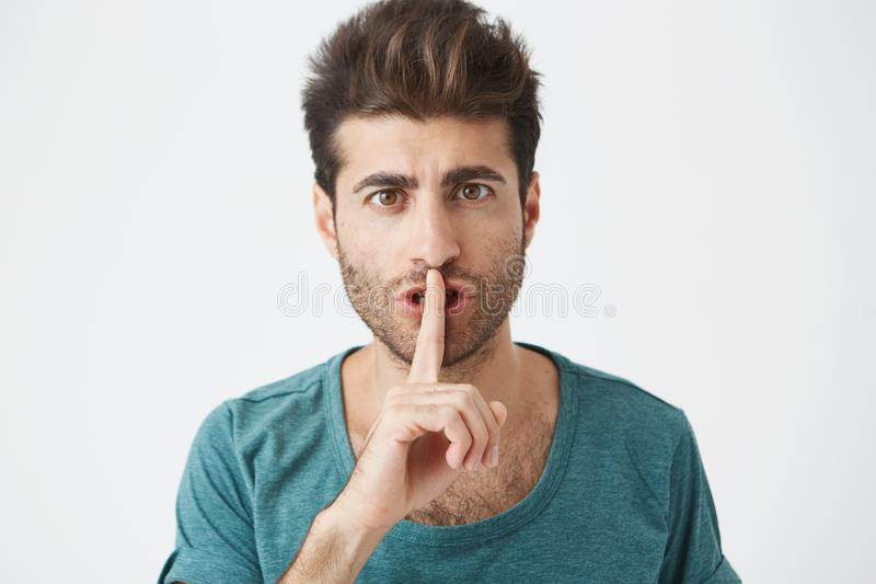 Headshot του ελκυστικού μοντέρνου καυκάσιου αρσενικού στην περιστασιακή μπλε μπλούζα, που κρατά το αντίχειρα στα χείλια, που ζητο στοκ εικόνες με δικαίωμα ελεύθερης χρήσης