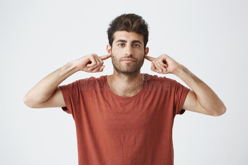 Headshot of annoyed stylish italian guy in red t shirt looking grumpy, closing ears with fingers showing disrespect on royalty free stock photos