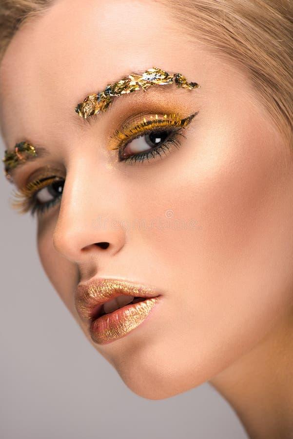 headshot atrakcyjna kobieta patrzeje kamerę z złotym błyskotliwym makeup obrazy royalty free