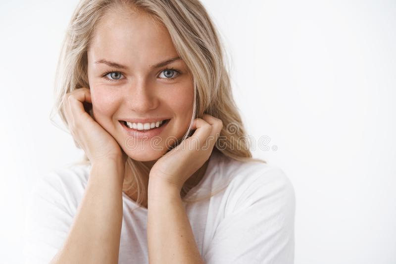 Headshot of attractive adult blond woman with tattoo leaning face on palms and smiling lovely making romantic gazes at royalty free stock photos