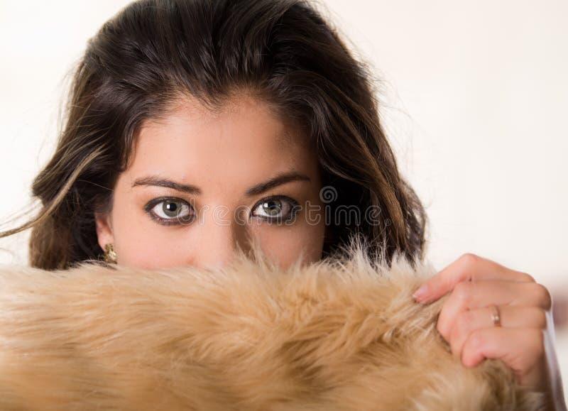 Headshot attraktiver Brunette, der ihre Gesicht der Kamerabedeckung Hälfte mit brauner Pelzkleidung, weißer Studiohintergrund geg lizenzfreie stockfotografie