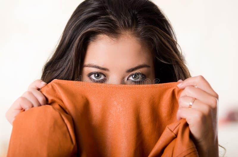 Headshot attraktiver Brunette, der ihre Gesicht der Kamerabedeckung Hälfte mit orange Kleidung, weißer Studiohintergrund gegenübe lizenzfreie stockfotografie