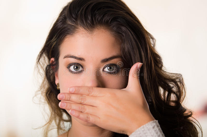 Headshot attraktiver Brunette, der ihre Gesicht der Kamerabedeckung Hälfte unter Verwendung einer Hand, weißer Studiohintergrund  stockfotografie