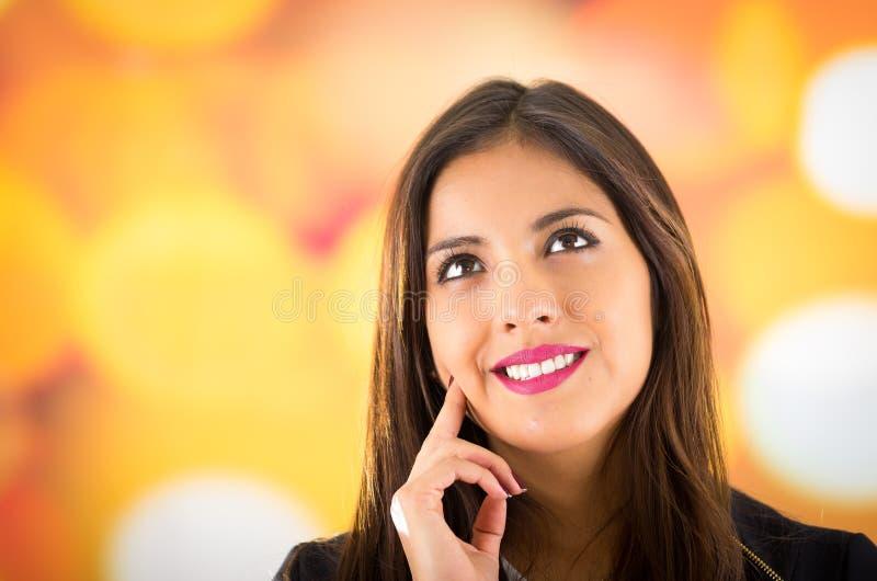 Headshot attraktiver Brunette, der natürlich mit schönem Lächeln, bunter undeutlicher Hintergrund aufwirft lizenzfreie stockbilder