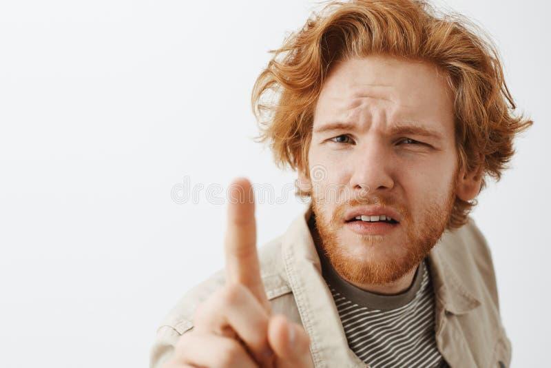 Headshot av den förvirrade och ifrågasatte roliga rödhåriga mannen med smutsigt hår och att uppsöka att skela, medan böja in mot  royaltyfria foton