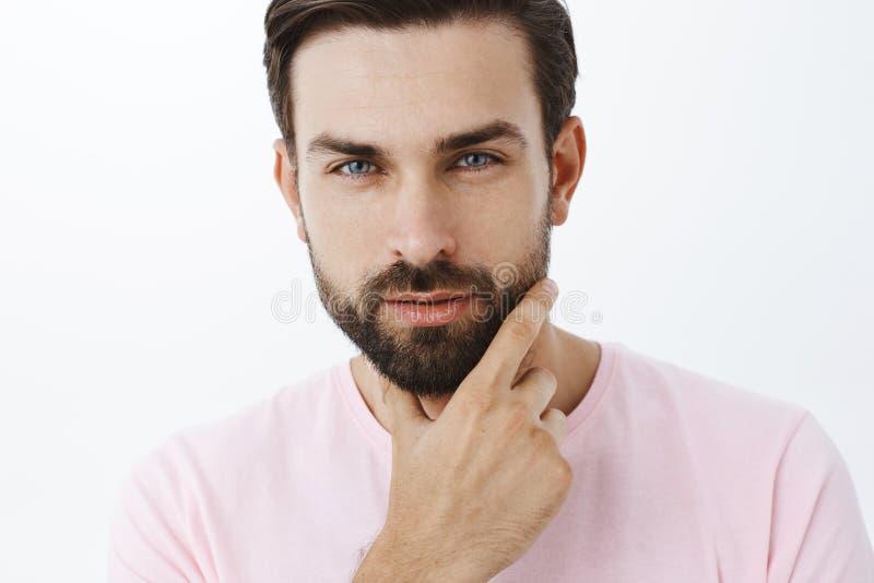 Headshot av den stiliga uppnosiga och sinnliga sexiga europeiska mannen med skägget och blåa ögon som skelar med lust och förföre royaltyfria foton