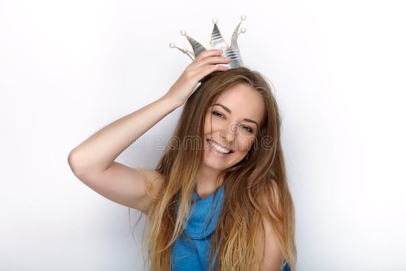 Headshot av den unga förtjusande blonda kvinnan med gulligt leende i handen - gjord prinsessakrona på vit bakgrund royaltyfri foto