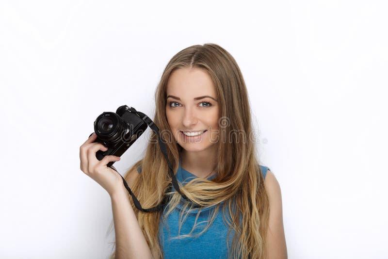 Headshot av den unga förtjusande skämtsamma blonda kvinnan med gulligt leende i koboltfärgblusen som poserar med den svarta dslrk arkivfoton
