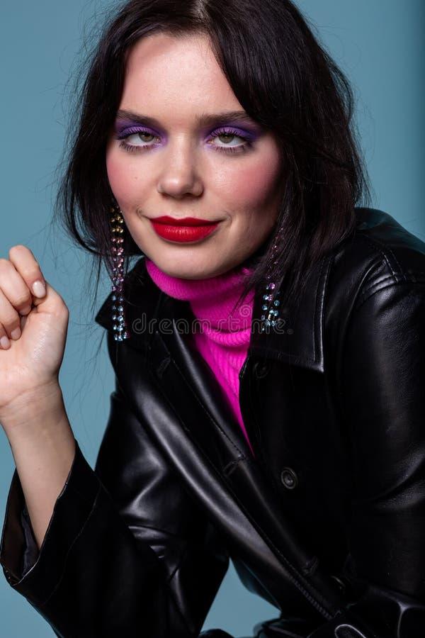 Headshot av densynade unga kvinnan för svart hår med färgrik makeup som grimacing arkivfoto
