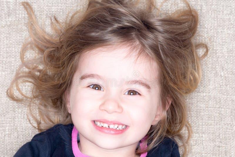 Headshot av unga flickan som ligger på en matta arkivfoto