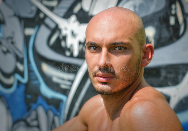 Headshot of bald young man shirtless outdoors royalty free stock images