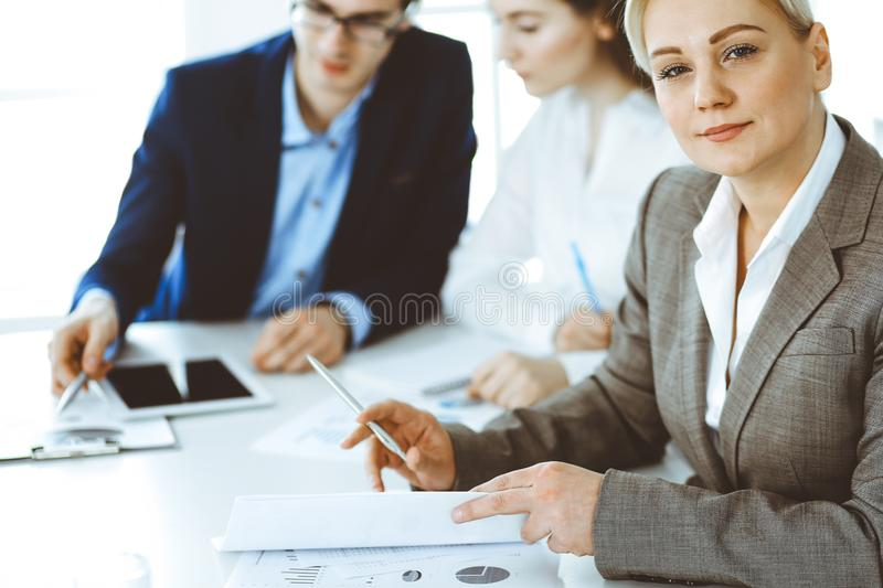 Headshot of business woman at negotiation. Group of business people discussing questions at meeting in modern office royalty free stock images