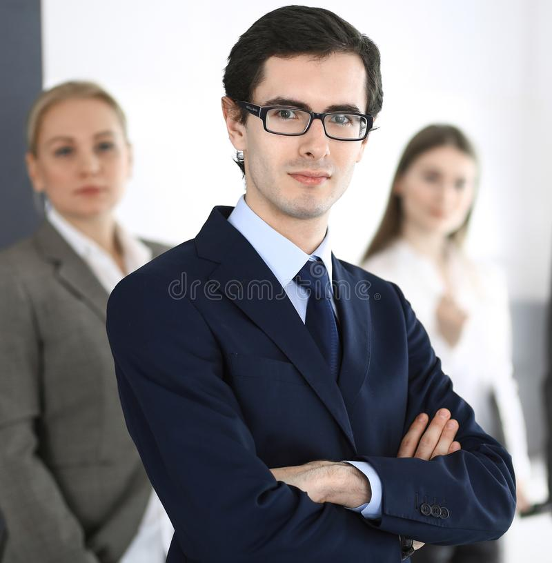 Headshot of businessman standing straight with colleagues at background in office. Group of business people discussing royalty free stock image