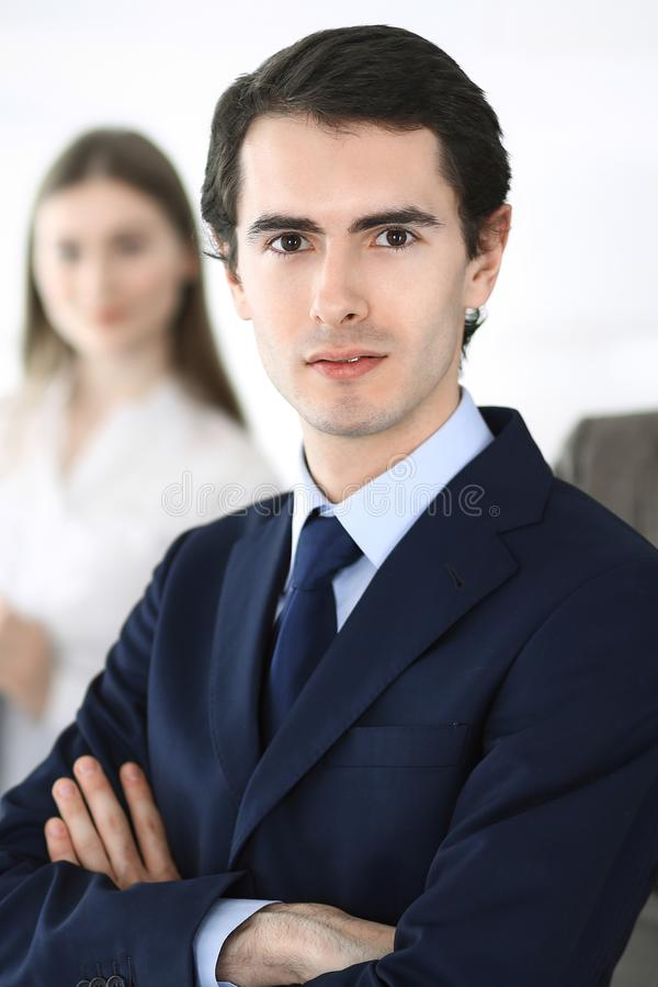 Headshot of businessman standing straight with colleagues at background in office. Group of business people discussing. Questions at conference or presentation stock photography