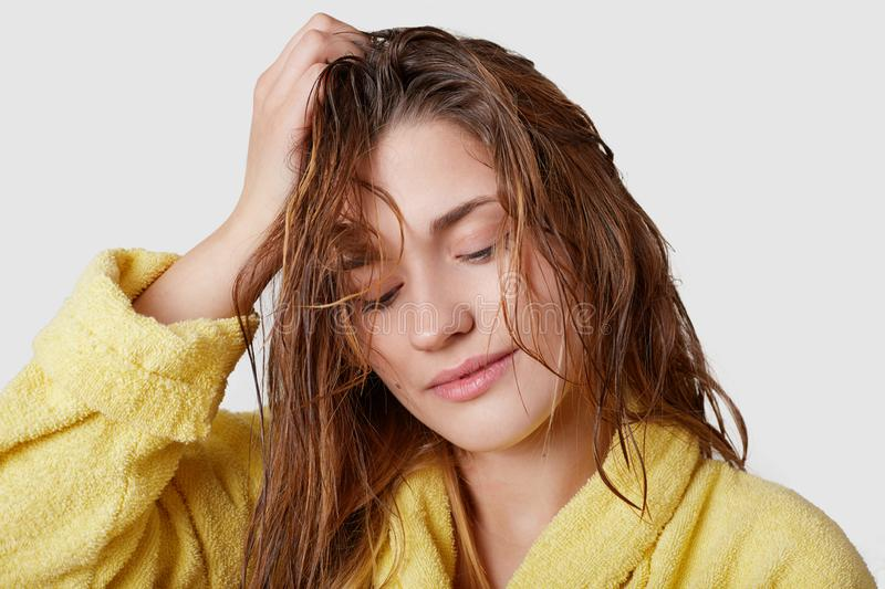 Headshot of charming thoughtful young female adult keeps gaze down, holds hand on head, has wet hair after taking shower, dressed stock photo