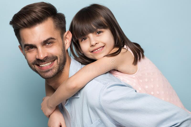 Happy young dad holding little preschool smiling daughter on back. royalty free stock photos
