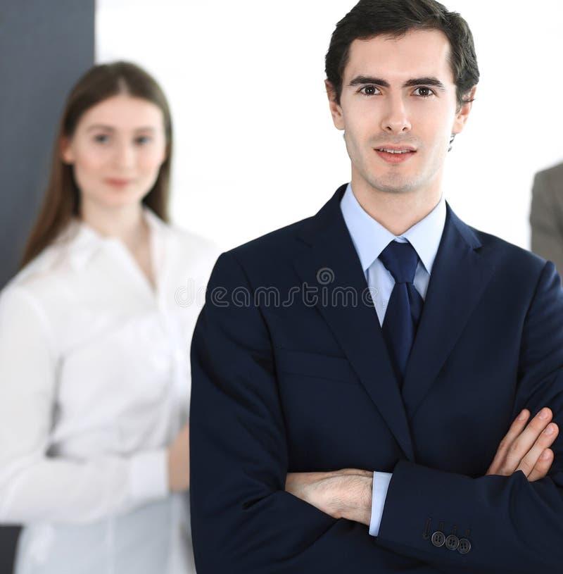 Headshot d'homme d'affaires se tenant directement avec des coll?gues au fond dans le bureau Groupe de gens d'affaires de discuter photos libres de droits
