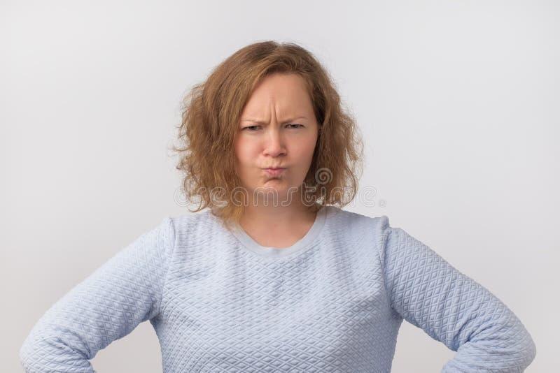 Headshot d'une jeune et fâchée femme dans le chandail bleu sur un fond gris Elle n'est pas satisfaite des résultats photo stock