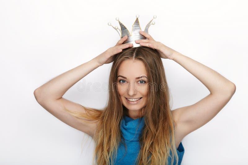 Headshot da mulher loura adorável nova com sorriso bonito na coroa feito à mão da princesa no fundo branco imagens de stock