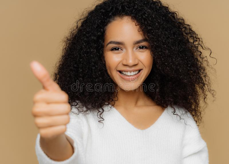 Headshot of dark skinned healthy curly young woman shows thumb up at camera, has pleasant smile, gives approval or likes idea, stock photos