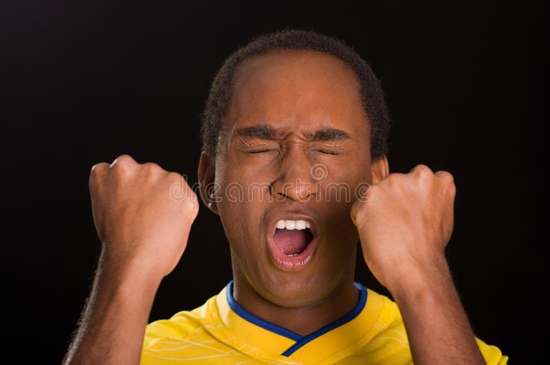 Headshot dark skinned male wearing yellow football shirt in front of black background, eyes closed and mouth open stock photos