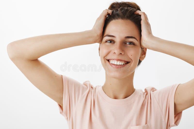 Headshot de jeune femme sensuelle et belle décontractée avec la peau pure propre touchant le chef insouciant et souriant doucemen photographie stock