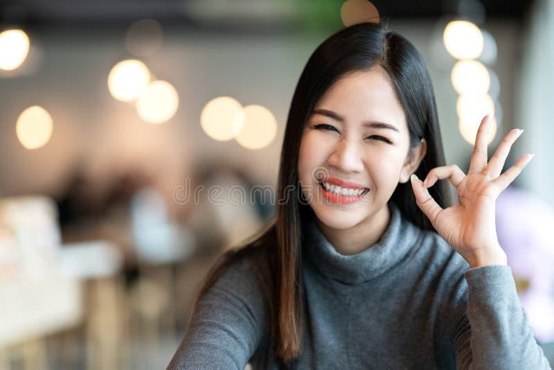 Headshot de la muestra linda de la autorización de la mano del gesto de la muchacha que siente positiva imagen de archivo libre de regalías