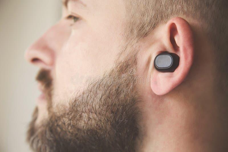 Headshot de plan rapproché du type caucasien européen beau utilisant les écouteurs sans fil et écoutant des dossiers ou parle image stock
