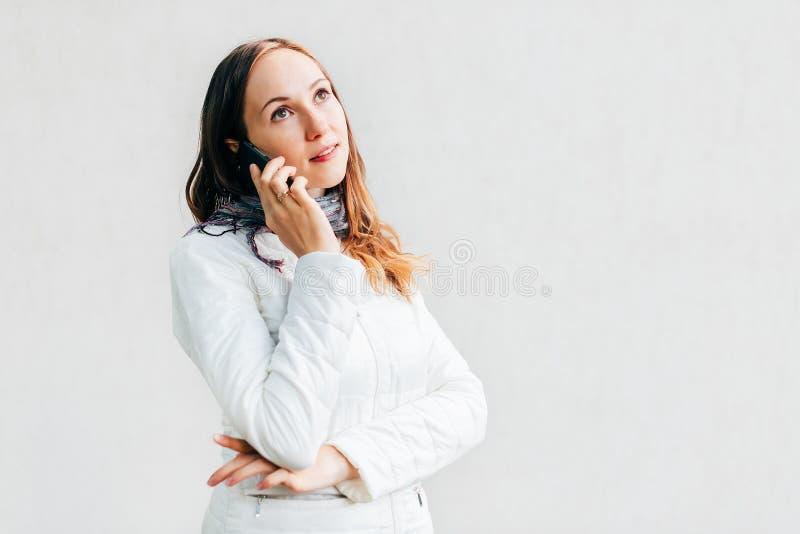 Headshot de portrait de jeune femme regardant loin pensivement et parlant au téléphone portable photographie stock libre de droits