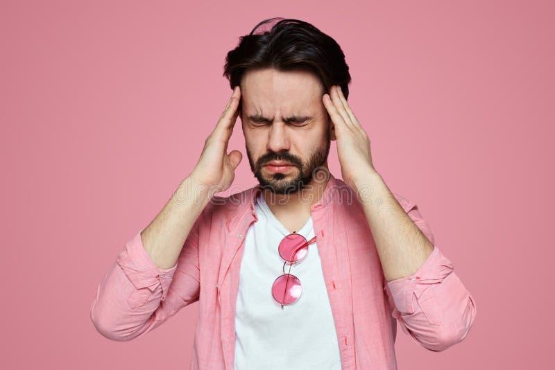 Headshot de um menino novo forçado vestido na camisa cor-de-rosa que tem uma dor de cabeça isolado sobre o fundo cor-de-rosa fotografia de stock