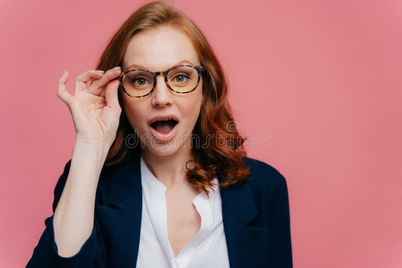 Headshot der überraschten roten behaarten Frau hält Hand auf Rahmen von Gläsern, Kiefer fallenließ, kann ihre Augen nicht glauben lizenzfreies stockbild