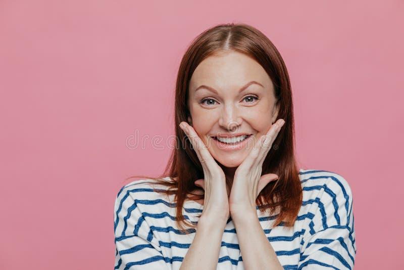 Headshot der attraktiven jungen Frau berührt Backen mit beiden Palmen, hat aufrichtiges Lächeln, trägt zufällige weiße und blaue  lizenzfreie stockbilder