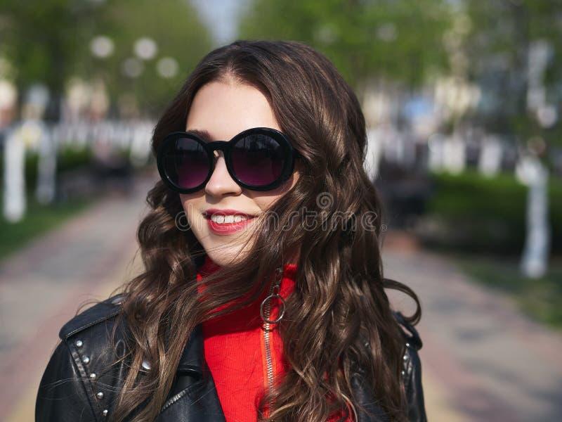 Headshot der jungen glücklichen modernen eleganten braunhaarigen Frau in der Sonnenbrille mit dem langen gelockten Haar warmes We lizenzfreies stockfoto