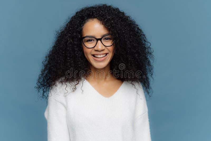 Headshot der reizenden gelockten Frau, die in der guten Laune ist, lächelt breit, drückt nette Gefühle aus, trägt transparente Sc stockbilder