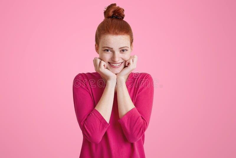 Headshot des erfreuten weiblichen Modells der Heiterkeit recht mit Ingwerhaarknoten, hat warmes angenehmes Lächeln, hält Hände un lizenzfreie stockbilder