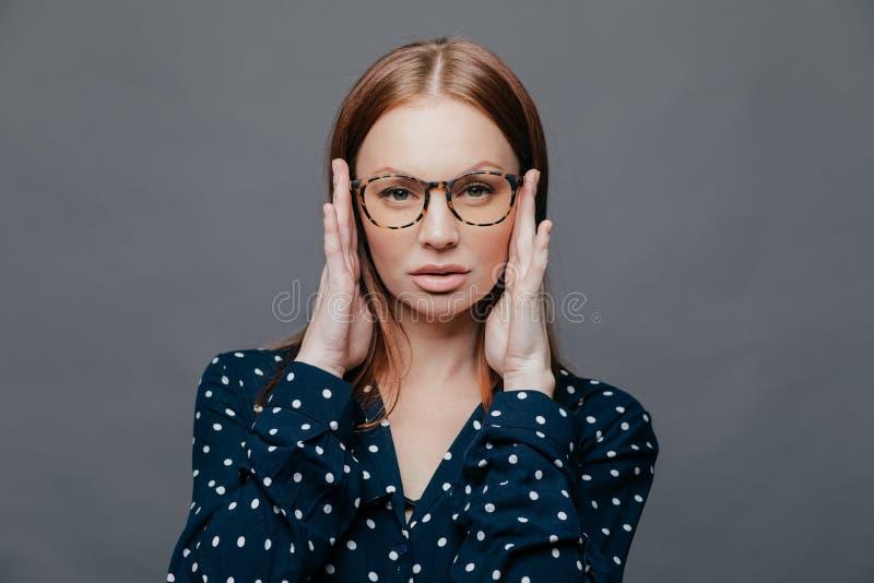Headshot des ernsten weiblichen Lehrers hält Hände auf Kopf, hat Selbstüberzeugten Gesichtsausdruck, trägt Schauspiele, den weiße stockfoto