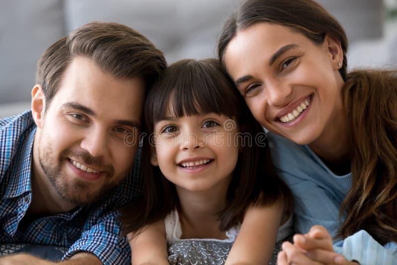 Headshot des glücklichen Abbindens der dreiköpfigen Familie, das Kamera betrachtet lizenzfreie stockbilder