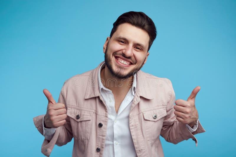 Headshot des hübschen jungen Mannes, der rosa stilvolle Jeansjacke trägt, Daumen oben über blauem Hintergrund lächelt und zeigt stockfotografie