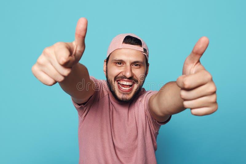 Headshot des hübschen jungen Mannes in der stilvollen Kleidung und in der bassebal Kappe, Daumen oben über blauem Hintergrund zei stockfoto