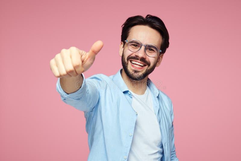 Headshot des hübschen jungen Mannes im blauen stilvollen Hemd und in den Brillen, die Daumen oben über rosa Hintergrund zeigen stockbilder