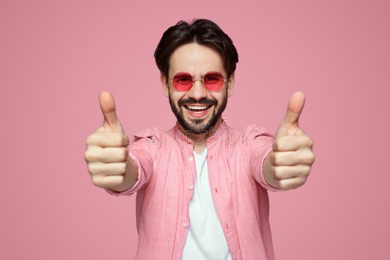 Headshot des hübschen jungen Mannes im rosa stilvollen Hemd und in der Sonnenbrille, die Daumen oben über rosa Hintergrund zeigt lizenzfreies stockfoto