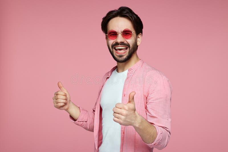 Headshot des h?bschen jungen Mannes im rosa stilvollen Hemd und in der Sonnenbrille, die Daumen oben ?ber rosa Hintergrund zeigt stockfotos