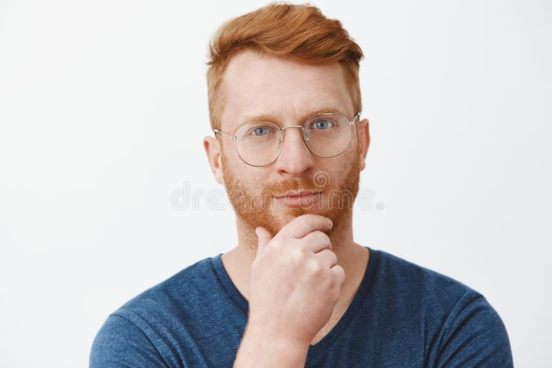 Headshot die van creatieve en slimme knappe roodharigekerel met varkenshaar in glazen en blauwe t-shirt, baard op kin wrijven en stock foto